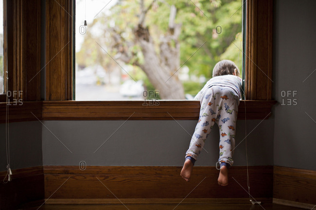 Young boy in pyjamas leaning out of a window