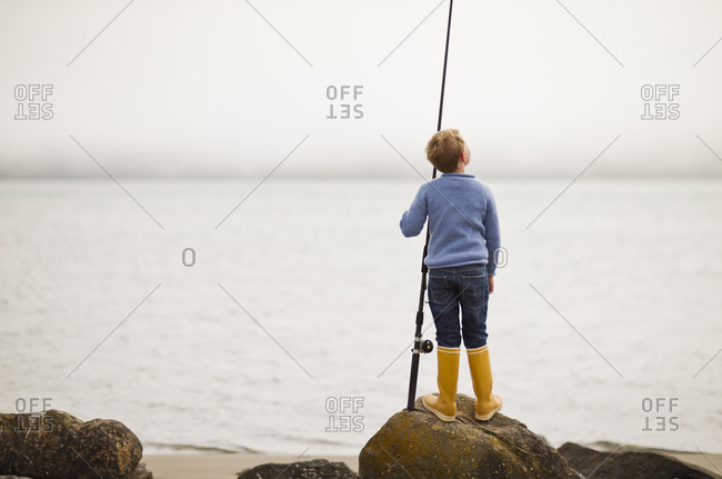 Young boy with his fishing rod on the beach