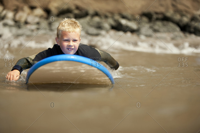 Young boy paddling on a surfboard