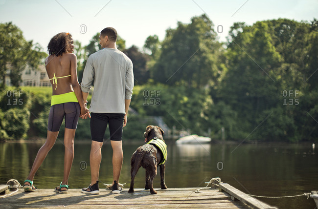 Couple standing at the end of a lake pier with their dog