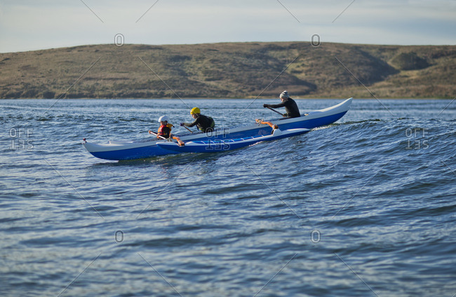 Team of canoeists catching a wave on an outrigger