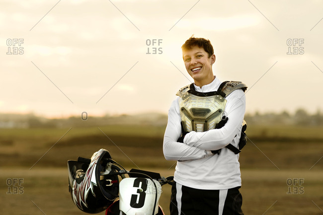 Smiling young man standing next to his dirt bike