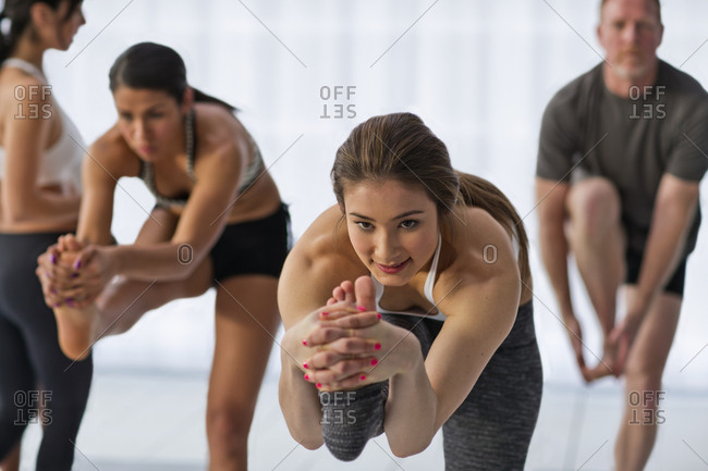 People standing on one leg during a yoga class