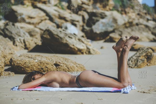 Woman lying on the beach without the bikini top