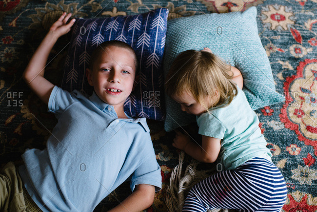 Brother and sister lying down on blue pillows on Persian rug.