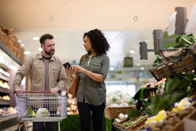 Couple buying vegetables in grocery store using smartphone