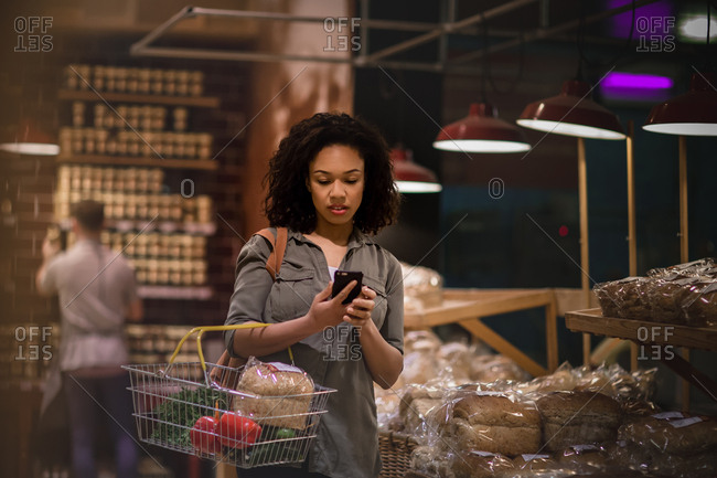 Woman late night grocery shopping and using smartphone