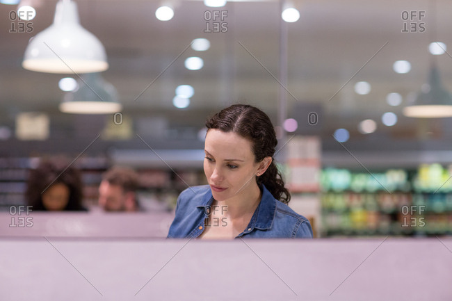 Woman looking at ready meal in grocery store