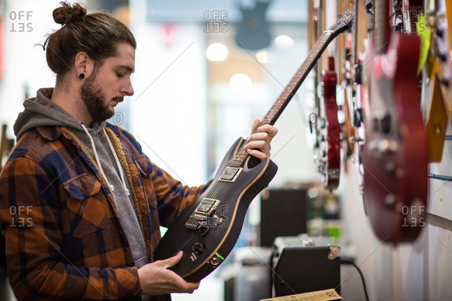 Young adult male looking at guitar in shop