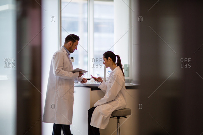 Female scientist discussing results of experiment with male colleague