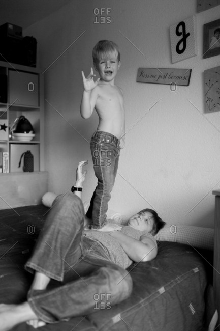 Boy standing on bed by mother