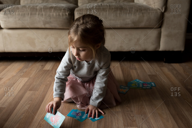 Girl playing a card game on the floor