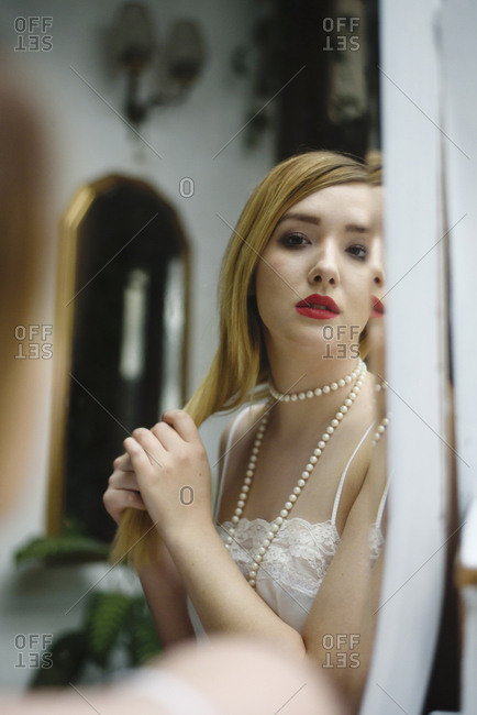 Beautiful young woman in laced underwear looking at vintage mirror