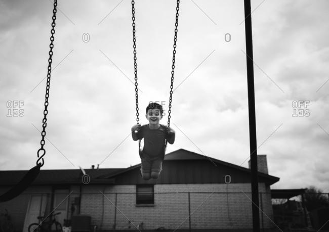 Smiling boy swinging high in swing