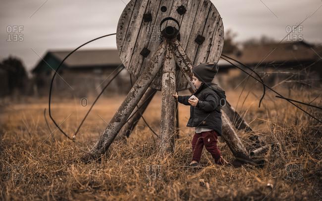 Little boy exploring old farm equipment in field