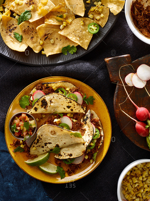 Tacos and nachos served on plates