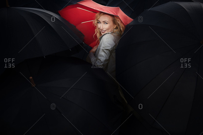 Woman holding red umbrella among a group of people with black umbrellas