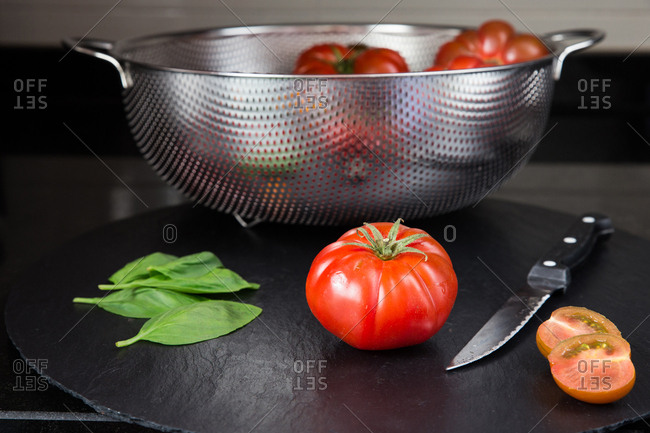 Still life of fresh red tomatoes on cutting board with knife near and leaves of basil.