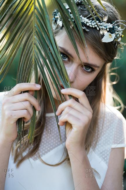 Portrait of gentle young girl in ornamental headband and dress posing behind palm leaf.