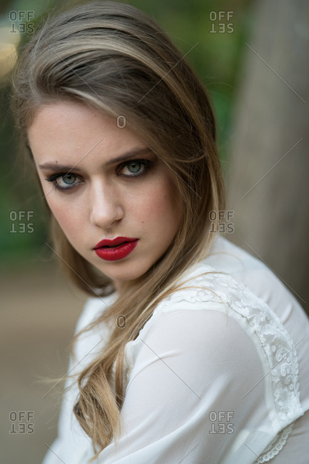 Young pretty female model in white blouse with strong makeup looking at camera.