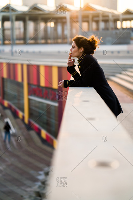 Young woman standing at the handrail and smoking. Vertical outdoors shot.