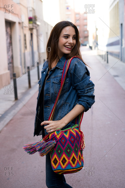Smiling young woman in the street posing with colorful knitted bag