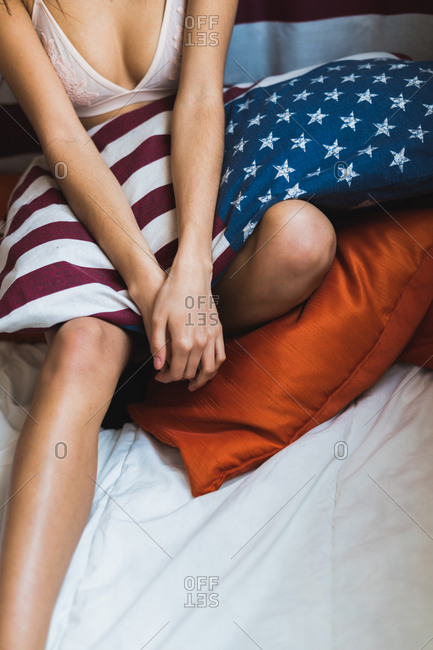 Crop photo of female wearing underwear sitting on bed with pillow with American flag print.