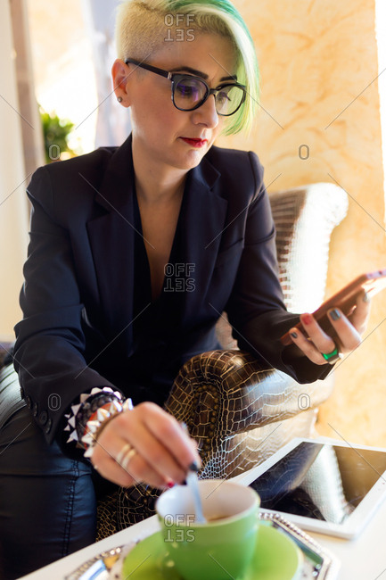Adult woman in formal wear stirring a drink and surfing the phone.
