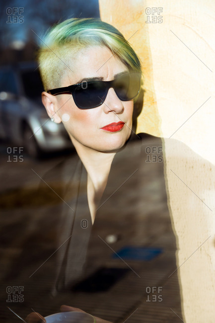 Vertical shot of mature woman wearing sunglasses looking through the window.