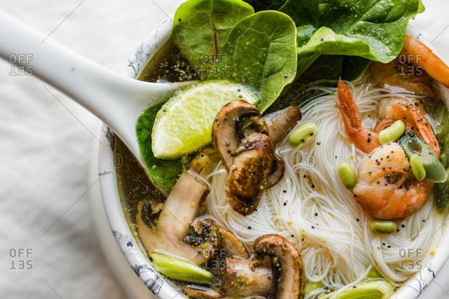 Bowl of Asian Noodle Soup with white ladle, closeup