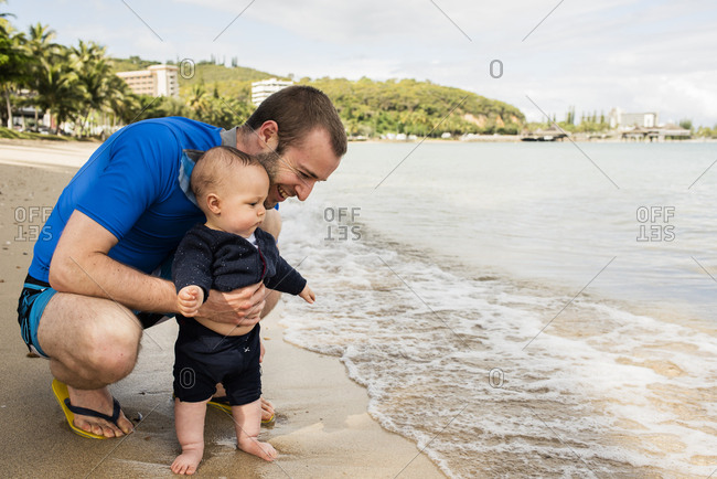 Baby seeing the ocean for the first time with his father