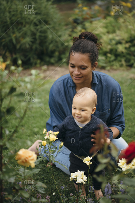 Mother and child looking at flowers in garden