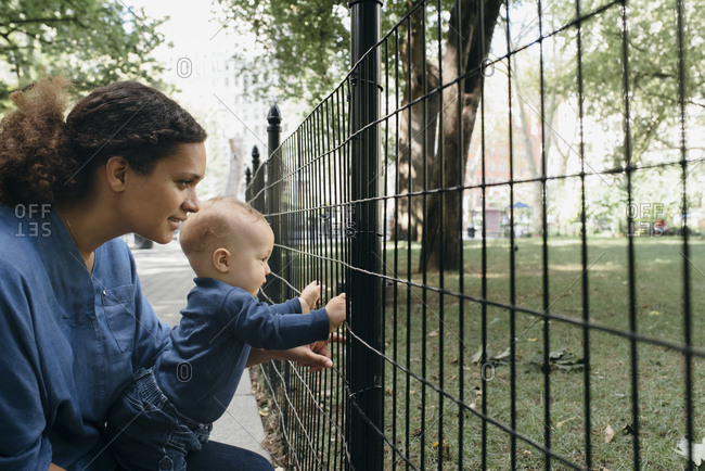 Mother and child looking through fence in new york city park