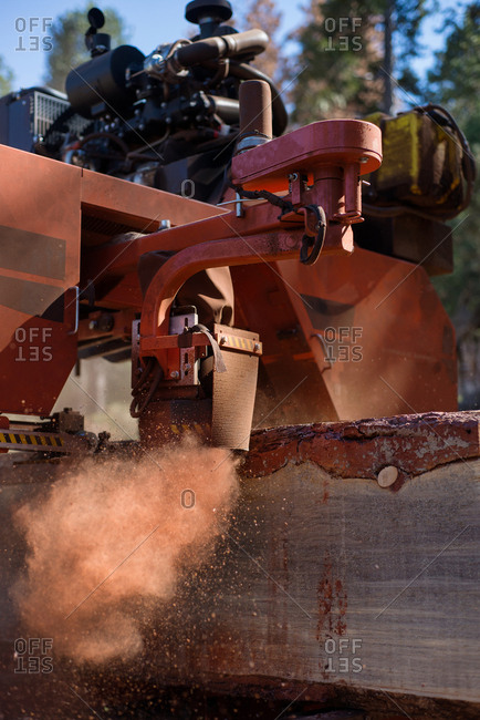 A close up of an industrial saw milling through a log with a plume of dust forming in its path