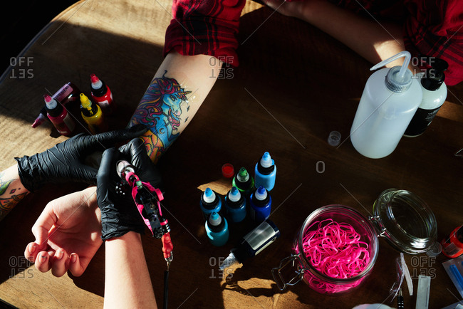 Creative tattoo ideas. High angle view of tattoo artist in rubber gloves tattooing colorful unicorn with electric tattoo gun on hand of female client