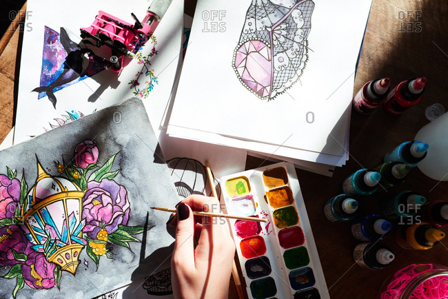 Unrecognizable female artist painting beautiful tattoo sketches with watercolors, high angle close-up view. Tattoo ink bottles and tattoo machine placed on table beside