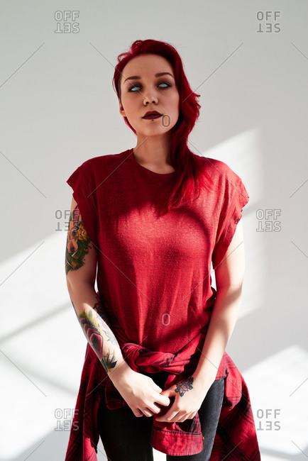 Portrait of young woman with dyed red hair, piercing and light blue eye contact lens standing on white wall background. Her hand covered with colorful tattoos