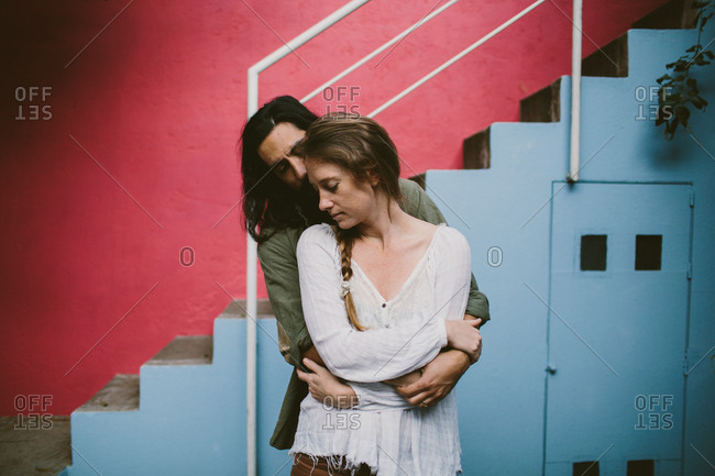 Couple embracing in front of colorful wall