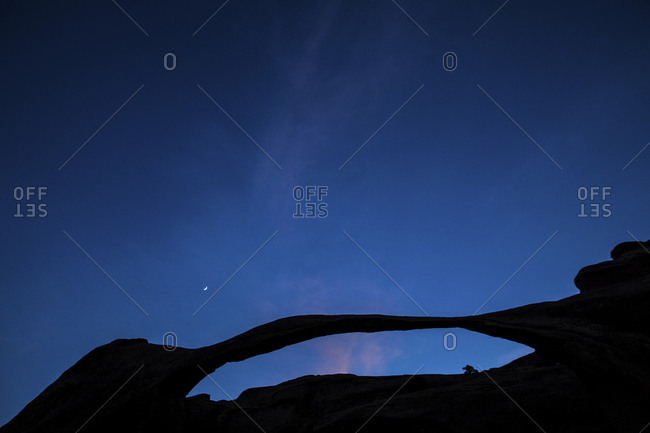 Crescent moon over silhouetted Landscape Arch in Arches National Park, Utah