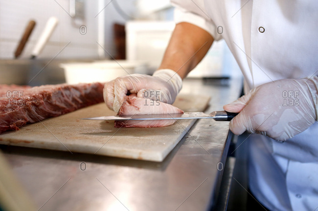 Butcher slicing meat on cutting board