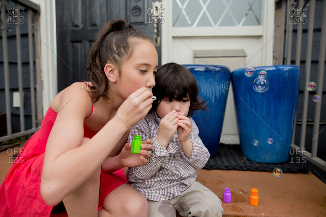 Toddler boy blowing bubbles with his older sister
