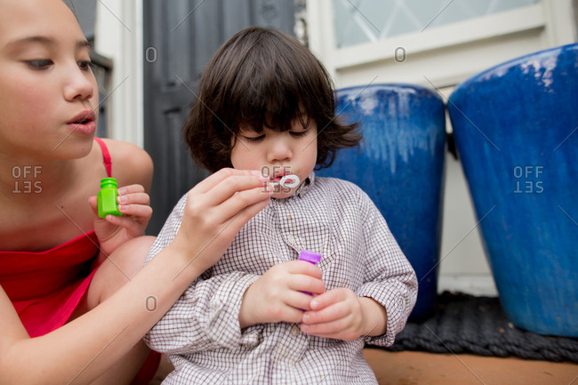 Girl holds wand while her toddler brother blows bubbles