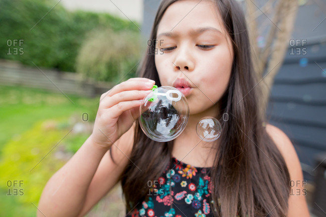 Young girl blowing bubbles in yard