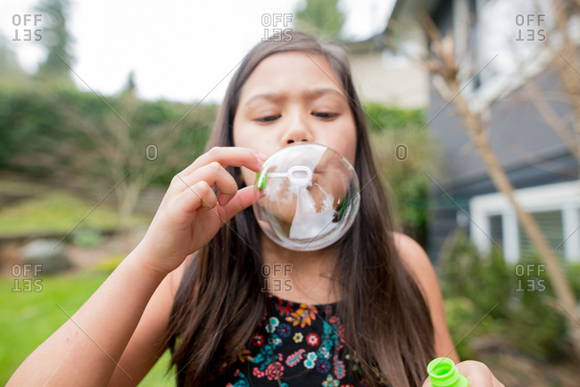 Girl carefully blows large bubble