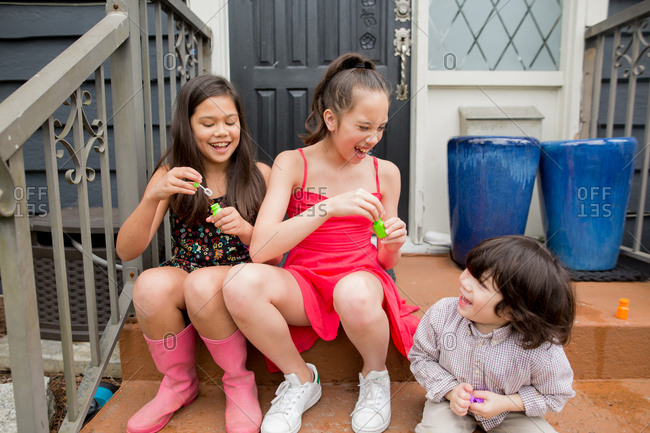 Three young siblings playing with bubbles on front porch