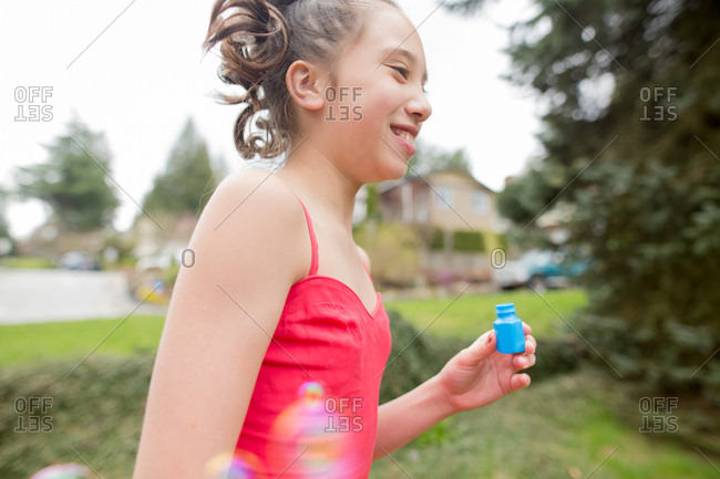 Young girl with small container of bubbles