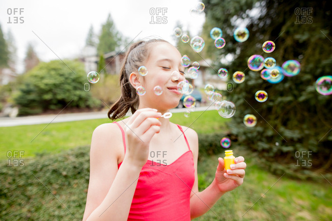 Happy adolescent girl blowing bubbles