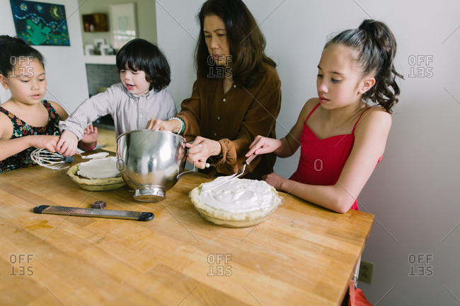 Children help their grandmother making chocolate cream pies