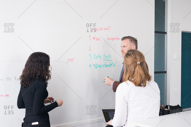 Colleagues in an office brainstorming on a whiteboard