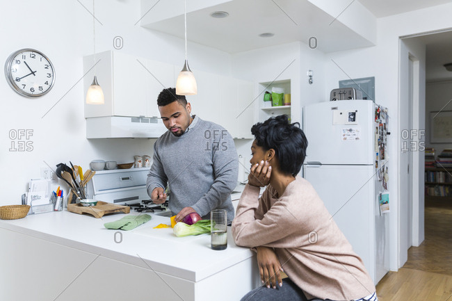 Man chopping vegetables while woman watches